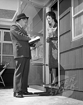 Young woman standing in a doorway and talking to a door to door salesman